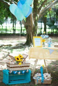 balões de hélio e cesta com girassóis em decoração de picnic azul tiffany e amarelo em praça. Chá de bebê com tema passarinhos.