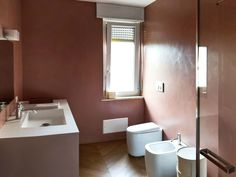 Colori armoniosi per il rivestimento del bagno in resina rosa antico in perfetta simbiosi con il pavimento in legno.