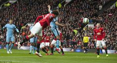 Fellaini leaps to meet man-of-the-match Ashley Young's superb cross with a thumping header...