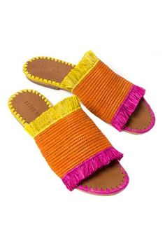 New Raffia Fringe Slide Sandal by Proud Mary. Crocheted woven raffia featuring yellow and brown fuchsia fringe, orange center and contrast side stitching. Handcrafted in Morocco.