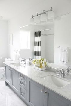 source: AM Dolce Vita  Gray Yellow Bathroom, Bianco Carrara floor, Vanity in Benjamin Moore Pigeon Gray, Bianco Statuario countertop, Kohler Fairfax lavatory faucets, Pottery Barn Mercer sconce, Benjamin Moore Chantilly Lace, West Elm Stripe Shower Curtain in Feather Gray, Stacked 4×16 white subway tiles Carrara border