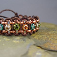 """multicolor crystal and leather wrap bracelet This leather wrap bracelet is unique as these Swarovski Crystals are one of its kind. It features Topaz, Light Colorado Topaz, Olivine (green), and Blue Zircon crystal buttons, distressed brown leather, antiqued copper plated rollo chain. It has a slide closure that is adjustable. Length is 7"""" and fits and average size wrist."""