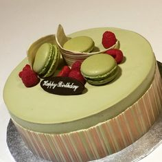 Matcha sponge cake layered with matcha mousse and azuki beans. Decorated with macarons, raspberries and a chocolate wrap.