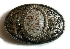 This womens Western belt buckle is made to go with a narrower belt. The textured flower relief background is a silver oval with a brown and white