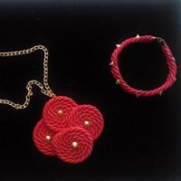 Necklace with red pendant and bracelets with studs.