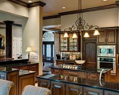Black glazed cherry cabinets accented with galaxy black granite countertops and metallic tile make this kitchen stunning and elegant.