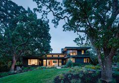 A modern house exterior with black-stained cedar siding.