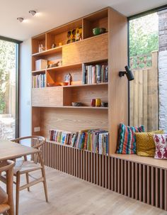 A tall bookshelf next to a window bench provides a place to display decor and a book collection.