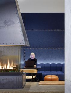 Studio BV has recently completed a lobby fireplace lounge that features rich blue felt wall panels that are stitched together with leather strips, complementing the custom-designed blue sofa and leather accents. #FeltWallPanels #FeltWallCovering #OfficeDesign #LobbyDesign #WorkplaceDesign #FeltPanels