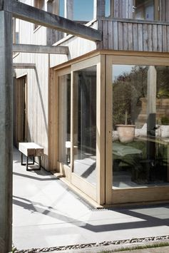 Wood framed sliding glass doors that meet on the corner, open the living room up to the backyard. #SlidingGlassDoors #WoodFramedGlassDoors