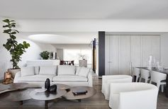 Modern living room with white sofa and armchairs.