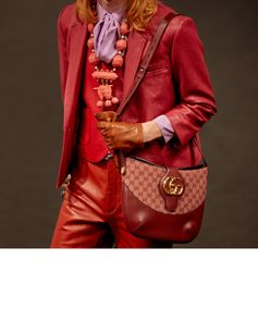 Captured before being presented on the runway at the Théâtre Le Palace in Paris, a men's leather jacket, pants and gilet from the Gucci Spring Summer 2019 fashion show by Alessandro Michele with a shoulder bag in GG motif.
