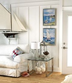 Beach cottage living room family room.  Love the white paneling and sailboat.