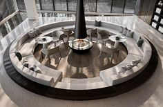 This modern sunken conversation pit, which was designed as a warm and pleasant space for potential customers to talk, offers custom seating that wraps around the interior of the circular shape, with enough room for small tables to also be included. #ConversationPit #SunkenSeating #InteriorDesign #Fireplace