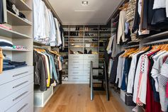 This modern walk-in closet has shelving, drawers, and plenty of space to hang clothes. #ModernWalkInCloset #WalkInCloset #Storage