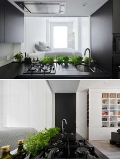 A matte black kitchen with a glass backsplash that acts as a window with views of the bedroom.