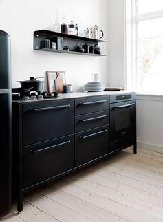 Cette petite cuisine noire est en parfait contraste avec le parquet en bois clair qui recouvre le sol.