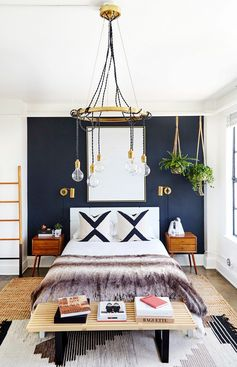 Glam bedroom with a black contrast wall, a chandelier, and layered rugs