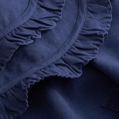 An informal take on the elegant cape, this design is cut from a soft, washed ramie cotton, for a lived-in look. The feminine piece is complete with ruffles that frame the collar and trim the undulating hem.