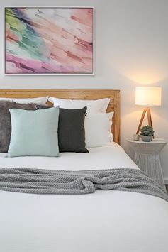 Master bedroom, white bedding, timber queen bed frame, cross floor rug, faux fur cushion, white wire side table, feather canvas, shaynna blaze artwork