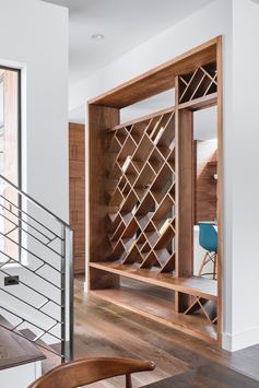 A custom entryway bench that has see-through diagonal wood shelving above.