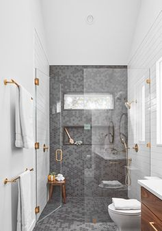 A modern shower with grey hexagonal tiles, a shower niche, and a frameless glass shower door.