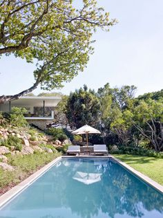 This modern house has stairs that lead from the patio, past a terraced rock garden, to the swimming pool and large grassy yard. #SwimmingPool #Landscaping