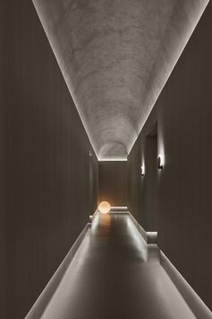 Indirect lighting showcases the curved ceiling and flooring in this hallway.