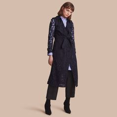 A trench coat crafted from macramé lace and lined in silk for a smooth fit. The elegant style features signature details such as epaulettes, gun flaps and a D-ring belt.
