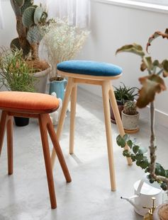 A modern wood kitchen stool with an upholstered cushion.
