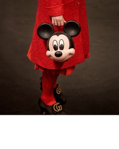Women's tailoring shot before being presented in the Gucci Spring Summer 2019 fashion show, a pleated skirt and coat worn with pumps with GG hardware and a bag shaped in the form of Mickey Mouse by Alessandro Michele. © Disney