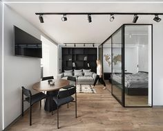 Located directly off the living room of this modern apartment, is a glass enclosed bedroom that provides separation from the rest of the apartment, but at the same time allows the natural light from the window to travel through to the bedroom. #GlassEnclosedBedroom #ModernApartment #BedroomDesign