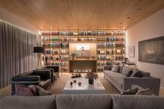 A living room wall full of shelving that has LED lighting to highlight the displayed decor and books.