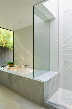A modern bathroom with a walk-in shower and a built-in bathtub with views of plants outside.