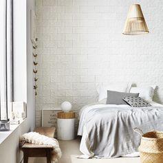 Une chambre avec des plaquettes de parement béton travertin blanc Motion. #homedecor #mur #ideedeco #chambre #bedroom #homedesign #lustre #coussin #lit #white #blanc #plaquettedeparement #leroymerlin