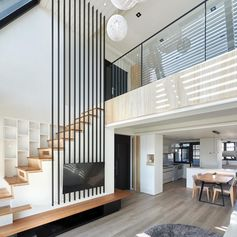 Interior design firm INDOT has designed a modern apartment in Taiwan, that features a bold collection of 12 black poles that travel from the living room up to the high ceiling. #HighCeiling #TVMount #StairDesign