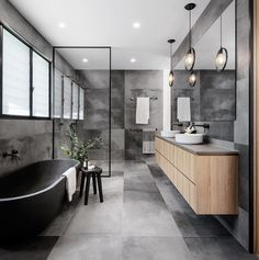 A modern master bathroom with a grey color palette, a freestanding bathtub, and a shower for two.