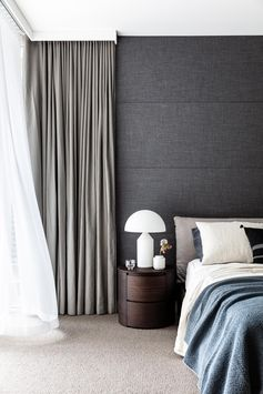 In this master bedroom, a charcoal wall and grey curtains create a bold accent for the space.