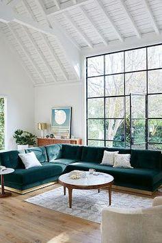 Canapé bleu canard, parquet clair et façade vitrée