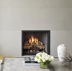 A grey fireplace surround, which travels from the floor to the ceiling,  contrasts the black frame and dark brick of the fireplace