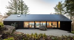 A modern black house with a black roof and Shou Sugi Ban exterior siding.