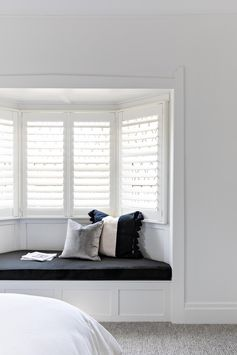 A bay window a custom designed window seat and black upholstered cushion.