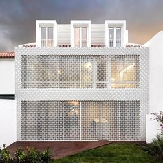 White patterned screens add a decorative element to this house, as well act as a sunlight filter and a security screen
