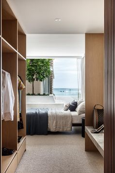 This modern walk-in closet has plenty of storage for clothes, and also includes a stone bench by the window.