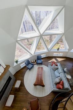 The newly updated interior of this geodesic dome house features bright white walls and modern furnishings feature throughout, like in the living room. The fireplace, which sits next to a large section of windows, has a limestone surround topped with a custom oak mantel that complements the hardwood flooring. #GeodesicDome #LivingRoom #Fireplace #TriangleWindows #InteriorDesign