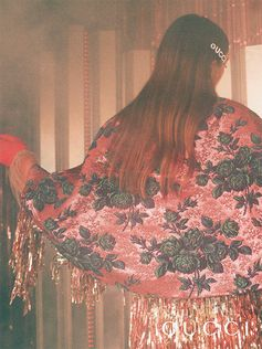 Seen in the new Gucci Gift campaign, an embellished cape featuring a colorful floral brocade with shiny lurex, from Cruise 2019.