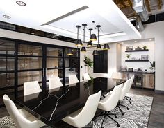 This modern conference room makes use of a suspended ceiling to partially hide the exposed ducting above and allow for the incorporation a statement light fixture. #InteriorDesign #SuspendedCeiling #CeilingDesign #Lighting #Workplace #ConferenceRoom