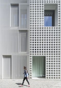 The cross-pattern facade of this modern buidling is made from pre-cast concrete and due to the design of the building, it's located between two other materials - white plaster and aluminum slats. #ModernArchitecture #ModernBuilding #PatternedFacade