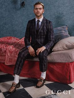 Featuring Alessandro Borghi in a checked suit and Horsebit moccasins, the Gucci Cruise 2018 campaign shot by Mick Rock, portraits of real people in real places.