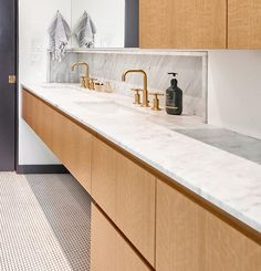 For the vanity in this modern bathroom, hardware free wood cabinets have been paired with light grey marble countertops, white under-mount dual sinks, and brass fixtures. #ModernBathroomVanity #MarbleVanity #BrassFixtures #WoodCabinets